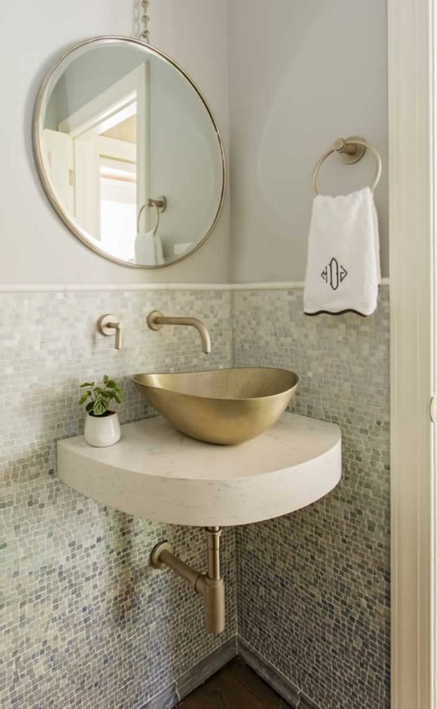 powder room with blue ombre mosaic tile, gold vessel sink on wall-mounted platform, and round mirror
