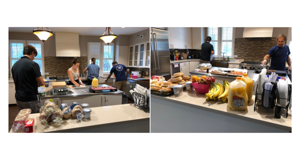Employees preparing breakfast of eggs, bacon, bagels and fruit